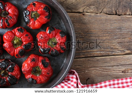 Roasted red bell peppers in a round pan, on an old wood board. Rustic take from above. Space for copy. - stock photo
