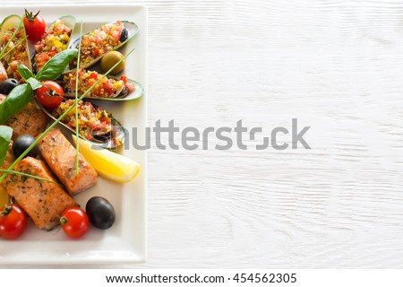Roasted red fish and stuffed mussels with lemon on white wooden background, copyspace for commercials. - stock photo