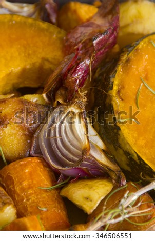 Roasted red onion on a bed of baked vegetables.
