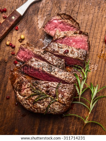 roasted  ribeye steak sliced ??on a cutting board with a fork ,rosemary and peppers, top view, close up - stock photo