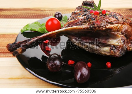 roasted ribs on black plate on wooden table - stock photo