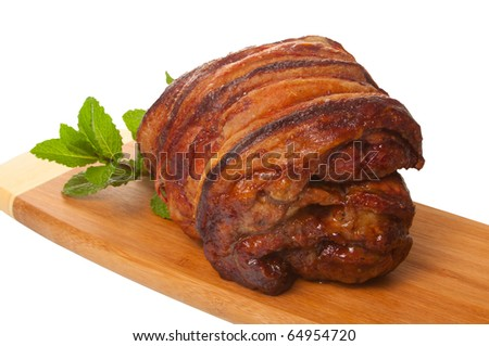 Roasted rolled shoulder of lamb on chopping board with mint, isolated over white background. - stock photo
