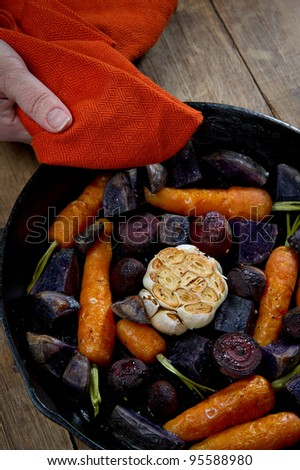 Roasted root vegetables in a cast iron skillet. Vegetables include carrots, red beets, garlic and purple potatoes.