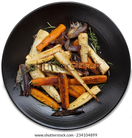 Roasted root vegetables in black platter, isolated.  Top view. - stock photo