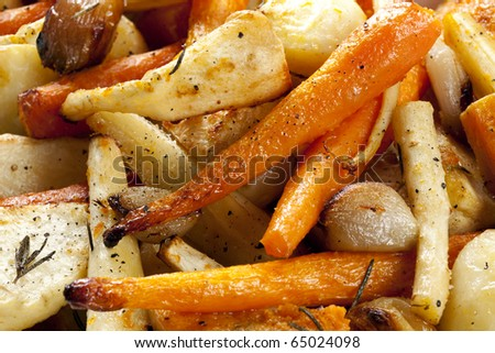 Roasted root vegetables, in close up.  Includes carrots and parsnips, plus potatoes, butternut squash, shallots and garlic bulbs. - stock photo