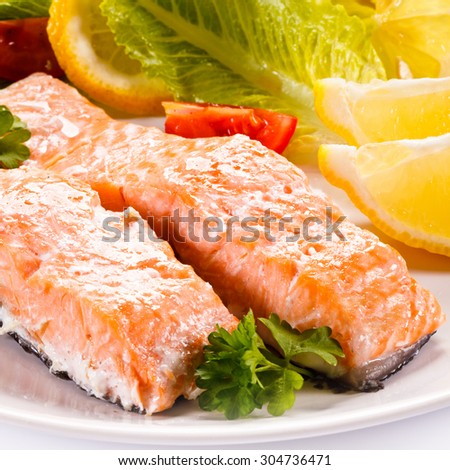 Roasted salmon and vegetables on white background