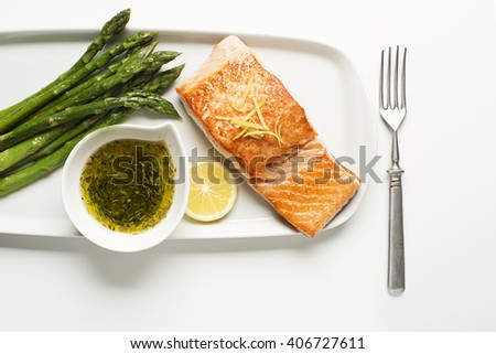 Roasted salmon fillet with asparagus on white - stock photo