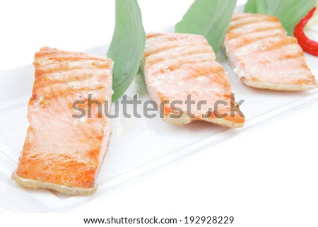 roasted salmon pieces with pepper and lemon on basil leaf over ceramic plate isolated on white background . shallow dof - stock photo