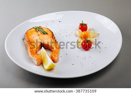 Roasted salmon stake plated with lemon and cherry tomato - stock photo