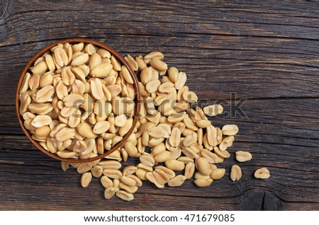 Roasted salted peanuts in bowl and near on dark wooden background, top view
