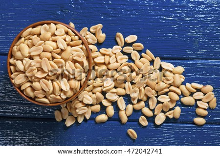 Roasted salted peanuts in paper on dark wooden background, top view