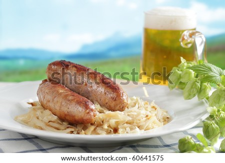 Roasted sausage with braised cabbage and beer against mountain background - stock photo