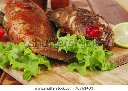 roasted sea fish and castors on wood with tomatoes, lemon and green lettuce salad . shallow dof