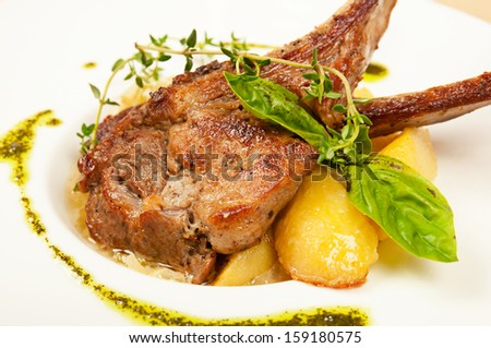 Roasted sheep meat with potatoes on dish  in restaurant - stock photo