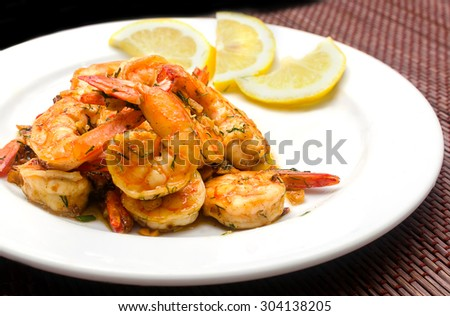 Roasted shrimps with garlic and herbs on white plate