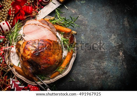 Roasted sliced Christmas ham on plate with fork, knife and festive decoration on dark rustic background, top view, border