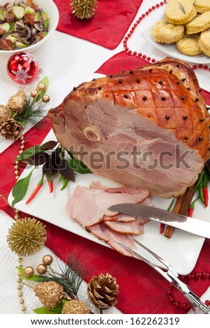 Roasted spiced ham on holiday dinning table, garnished with cloves, cinnamon sticks, hot chili pepper, and purple basil. Side dishes and Christmas ornaments around.  - stock photo