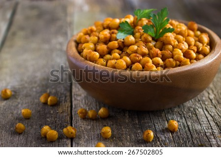 Roasted  spicy chickpeas on rustic background - stock photo