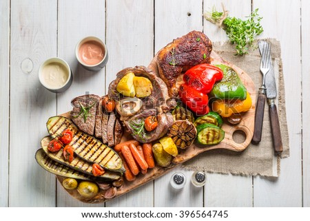 Roasted steak and vegetables with salt on wooden board - stock photo