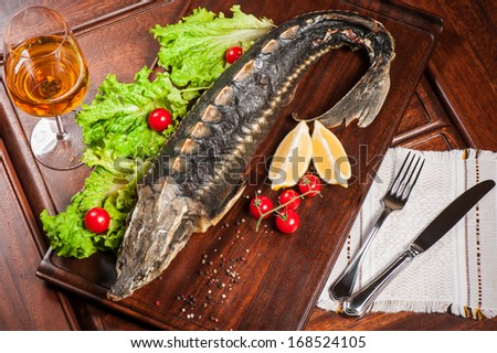 Roasted  sturgeon with cherry tomatoes and lettuce - stock photo