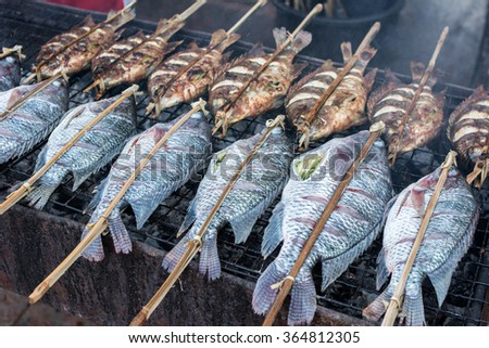 Roasted tilapia fish on grill, Salt Crusted Grilled Nile Tilapia Fish on Grate on charcoal stove Clear focus on specific areas of the image./ soft Focus - stock photo
