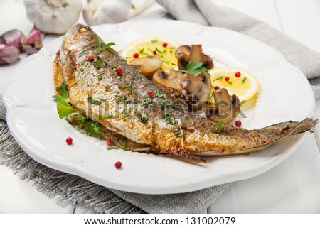Roasted trout on white plate with lemon pieces, and mushrooms on wooden table. - stock photo