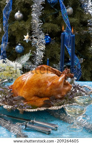 Roasted turkey garnished with herbs on blue Christmas decorations, and champagne. Christmas tree as background.  - stock photo