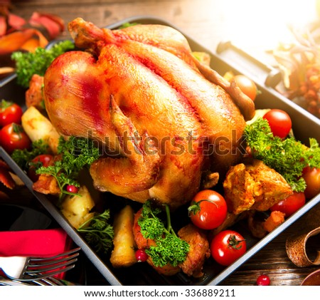 Roasted turkey garnished with potato, vegetables and cranberries on a rustic style table. Christmas or Thanksgiving Dinner - stock photo