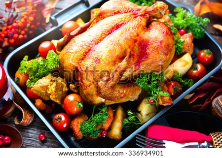 Roasted turkey garnished with Potato, Vegetables and cranberries on a rustic style table decorated with autumn leaves. Thanksgiving Dinner - stock photo
