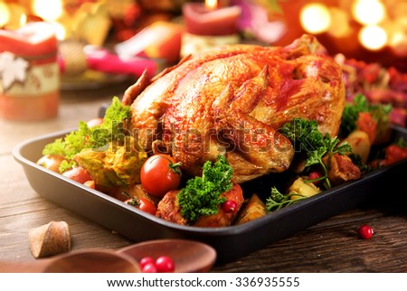 Roasted turkey garnished with Potato, Vegetables and cranberries on a rustic style table decorated with autumn leaves and candles. Christmas Dinner - stock photo