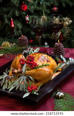 Roasted turkey garnished with sage, rosemary, and red berries in a wooden tray on Christmas decorated table. Candles and Christmas tree with ornaments.  - stock photo