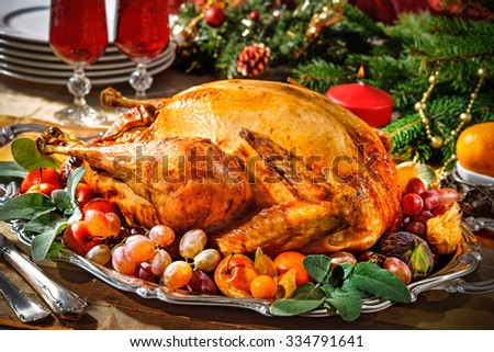 Roasted turkey on holiday table with candles - stock photo