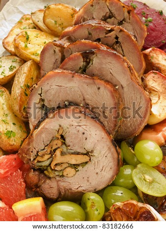 Roasted turkey roulade with potatoes, beet and fruits. Shallow dof. - stock photo