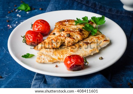 Roasted turkey steak with tomatoes, parsley and spice in white bowl on dark blue background. Selective focus. Toned image - stock photo