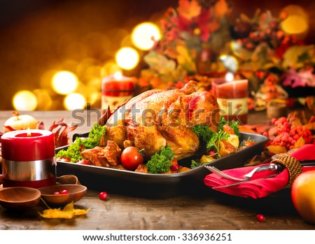 Roasted Turkey. Thanksgiving table served with turkey, decorated with bright autumn leaves and candles. Roasted chicken, table setting. Christmas dinner  - stock photo
