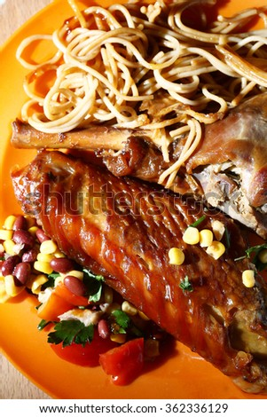 roasted turkey wings with spaghetti and salad on the plate - stock photo
