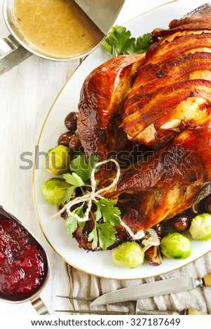 Roasted turkey with bacon and garnished with chestnuts and brussels sprouts. Prepared for Thanksgiving or Christmas dinner. - stock photo