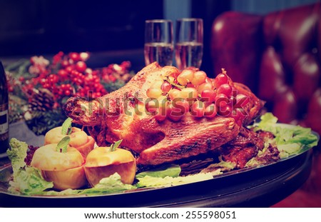 Roasted turkey with baked apples and grapes, festive dish, toned image - stock photo