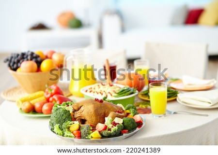 Roasted turkey with vegetables on holiday table with juice, garnish and other food served for Thanksgiving dinner - stock photo