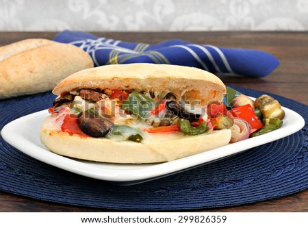 Roasted vegetable sandwich with melted cheese on a sub roll, close up.  Healthy vegetarian meal. - stock photo