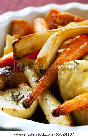 Roasted vegetables, including carrots, parsnips, shallots, potatoes, and butternut squash. - stock photo