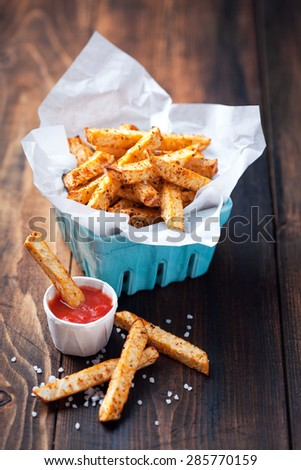 Roasted vegetables (potato and celery root) in ceramic basket and tomato sauce, selective focus - stock photo