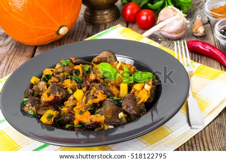 Roasted vegetables with pumpkin and mushrooms on a black plate. Studio Photo