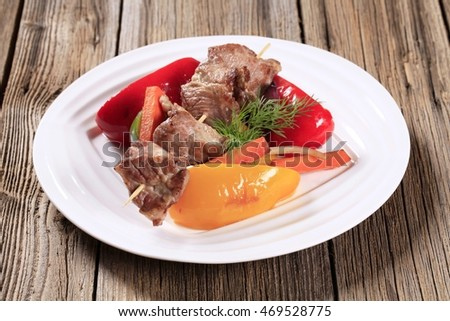 Roasted venison on a skewer and vegetables