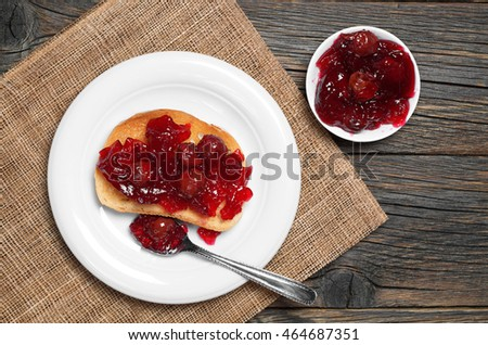 Roasted white bread with cherry jam in plate on rustic wooden table, top view