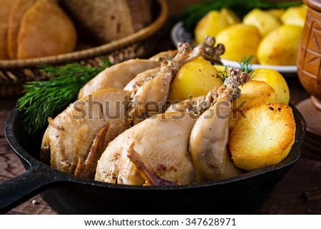 Roasted whole chicken and golden potatoes garnished with fresh dill in iron skillet. Potato salad and fresh sliced bread on background. Country style dinner. Close up - stock photo