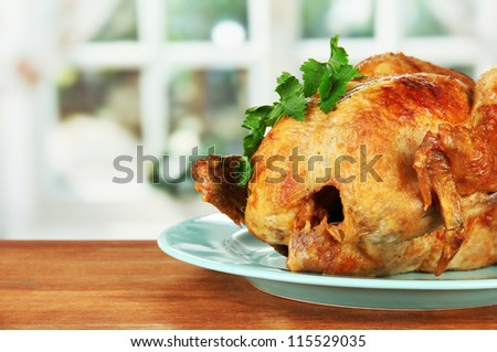 Roasted whole chicken on a blue plate on wooden background close-up - stock photo