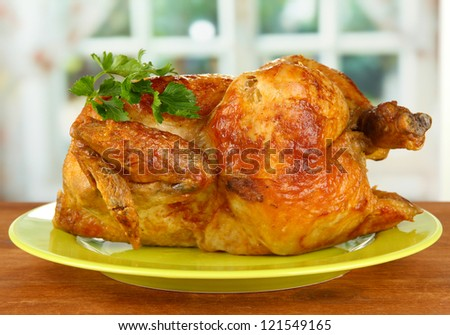 Roasted whole chicken on a green plate on wooden background close-up