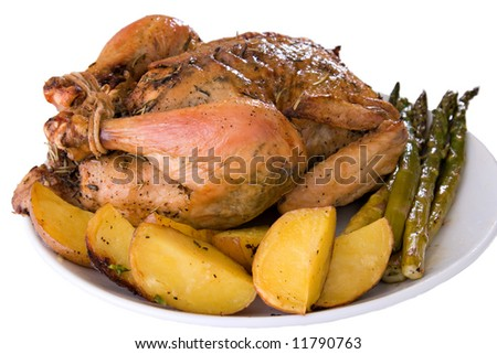 Roasted whole chicken on a plate with fried potato and asparagus - stock photo