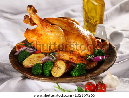 Roasted whole chicken on a plate with vegetables - stock photo